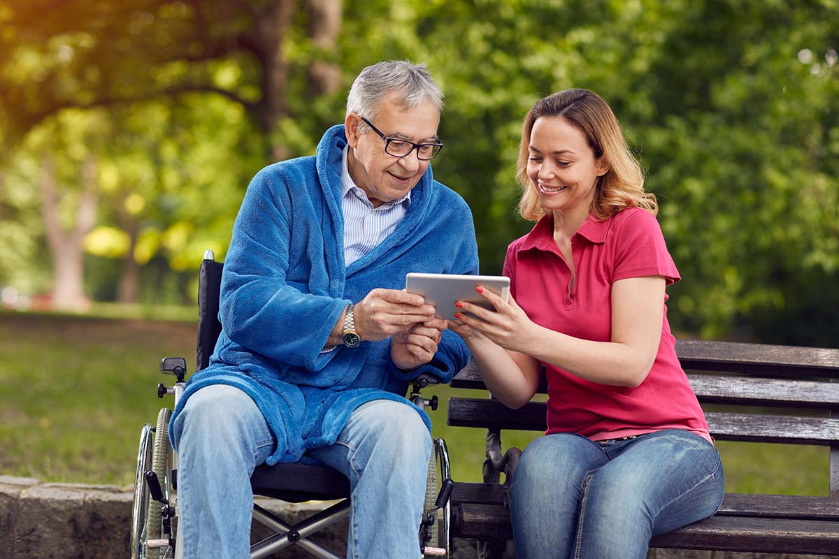 Caregiver helping a senior to use a tablet