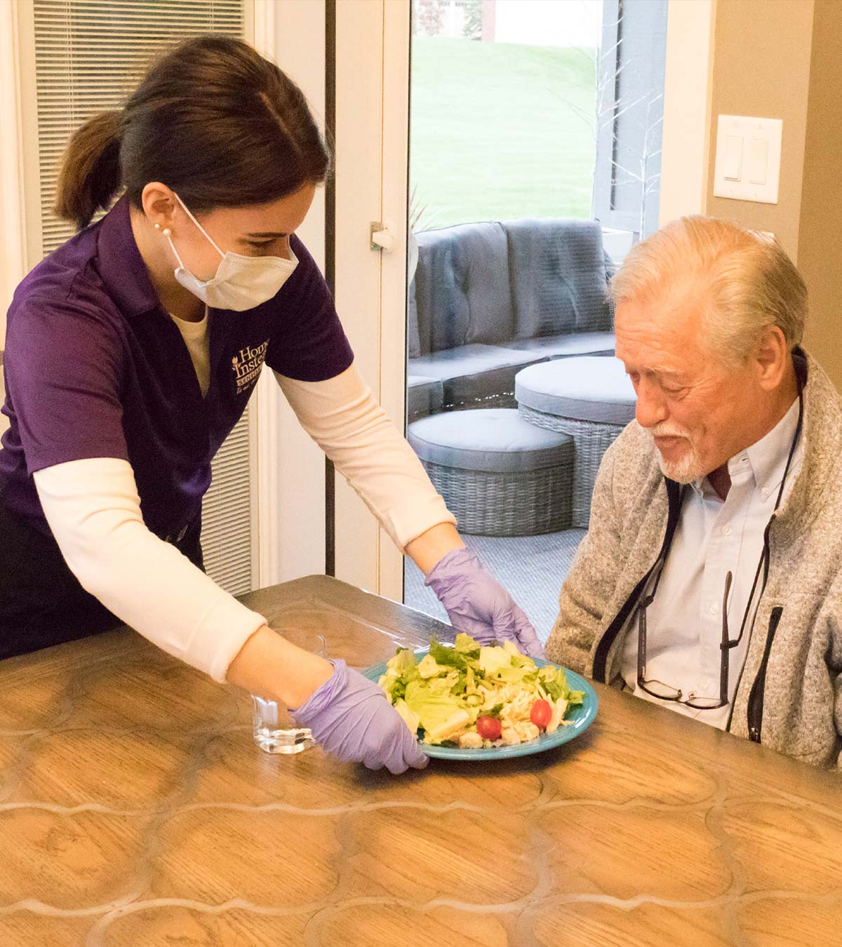A masked Home Instead Caregiver is serving a nutritious meal to a senior