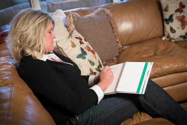 Family Caregiver taking notes in a book