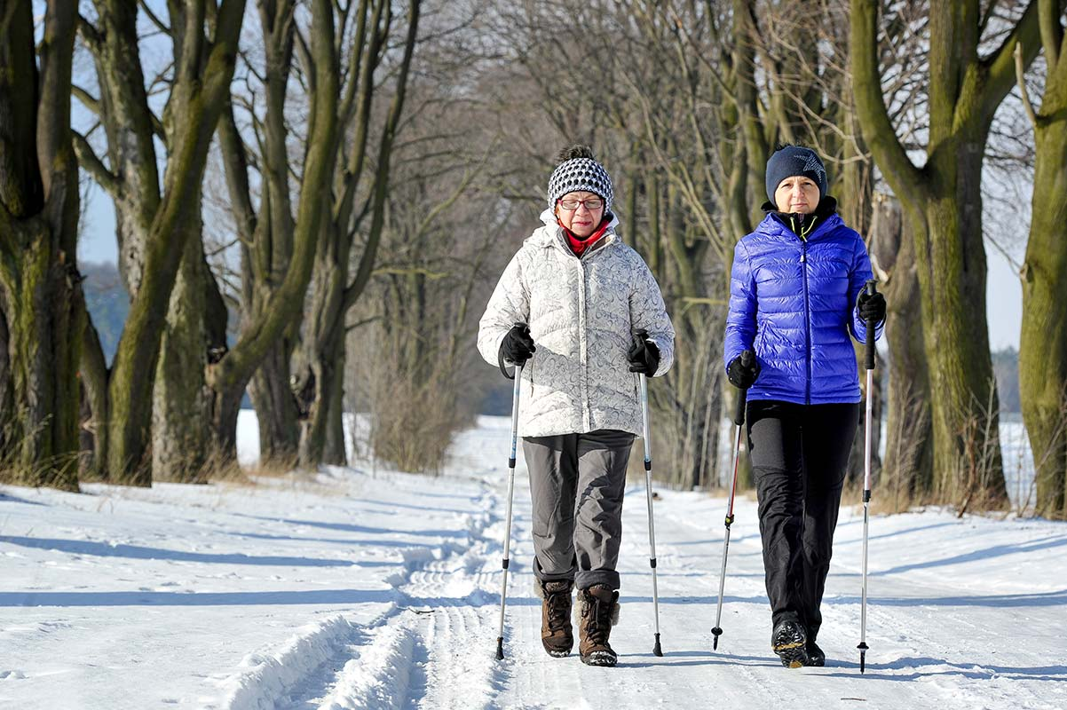 Senior and Caregiver during Nordic walking for fun and exercise
