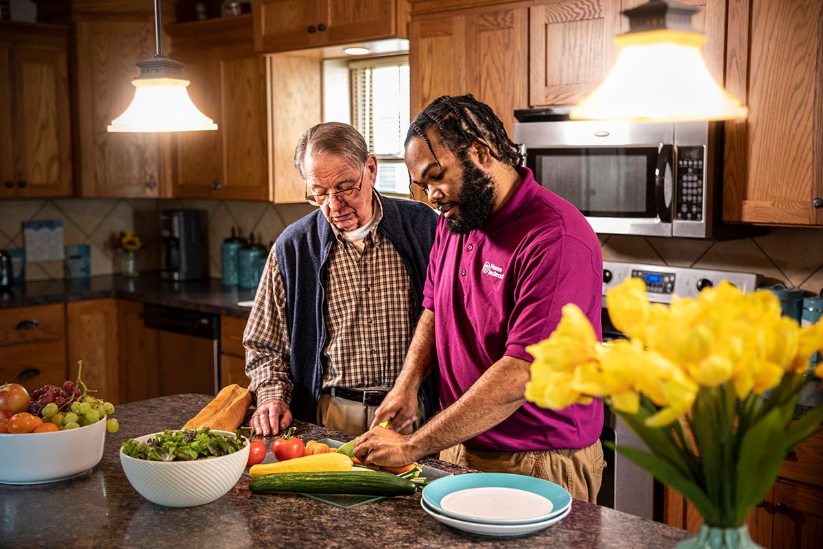 Home Instead Caregiver and senior man prepare a healthy meal together in kitchen