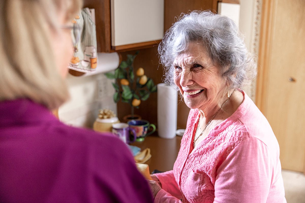 Senior woman smiling while standing in kitchen at home