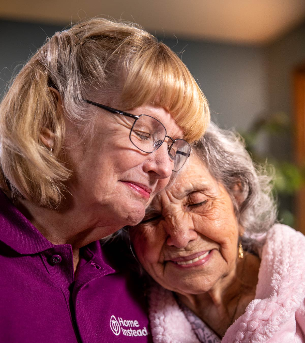 Home Instead CAREGiver and senior sitting together compassionately