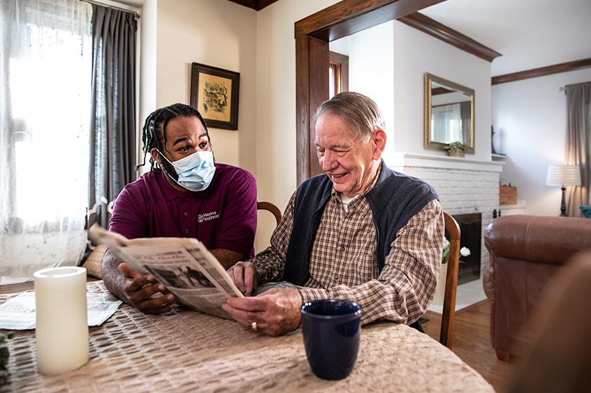 Home Instead Caregiver wearing mask reading newspaper with senior man at home