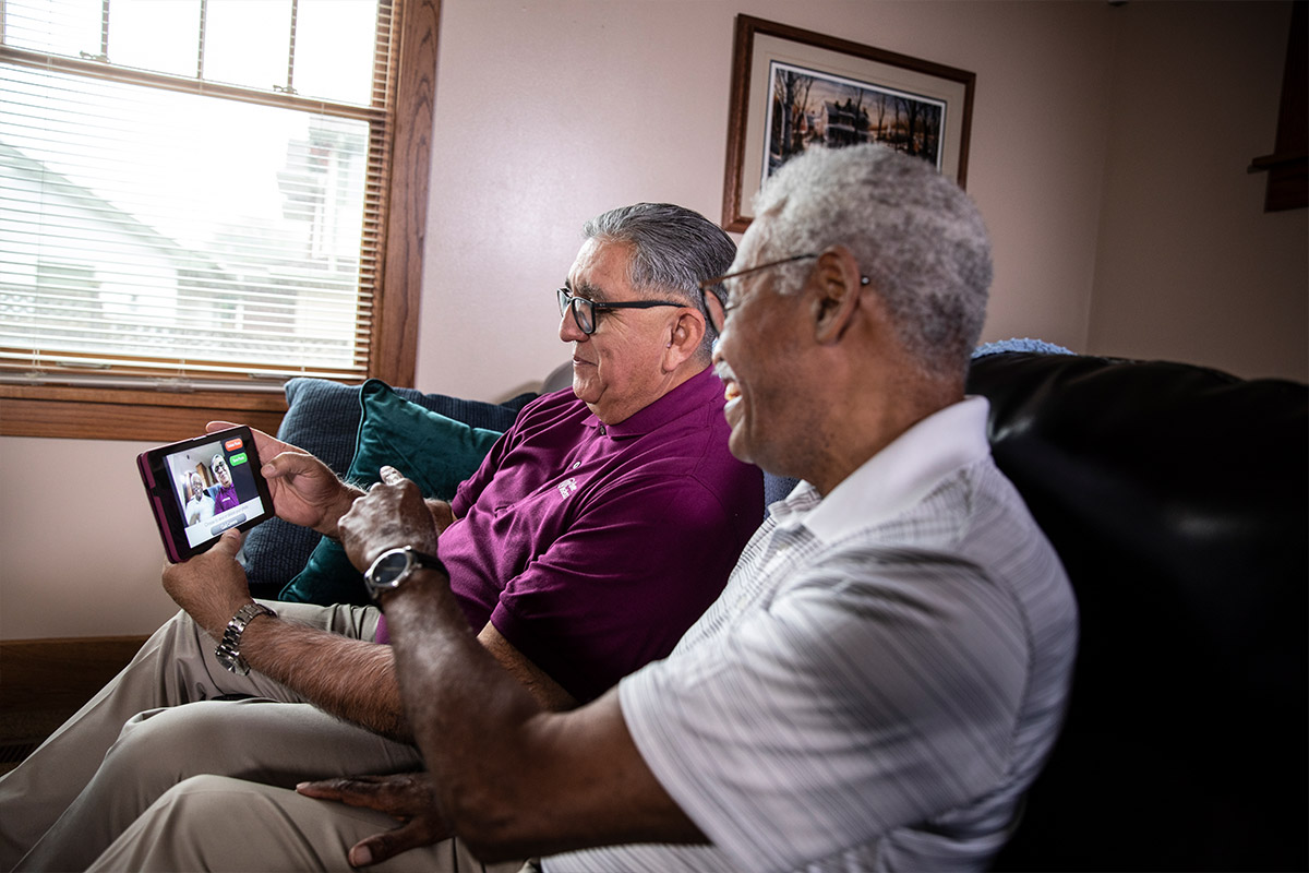 Home Instead Caregiver helps senior man with video conference call at home using tablet