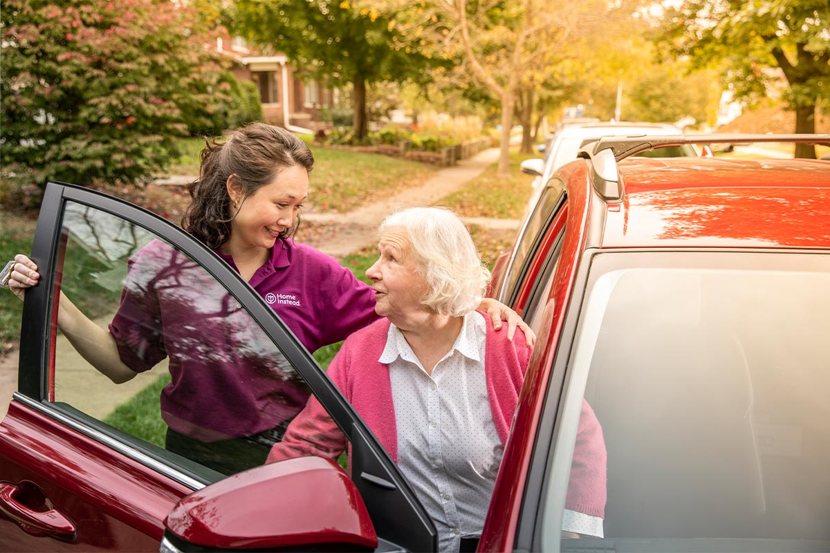Home Instead Caregiver helps senior woman getting out of car